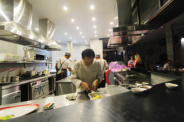 The grill kitchen Chef Jason Lee plates while a guest views the fresh meat and fish Fire Walker display